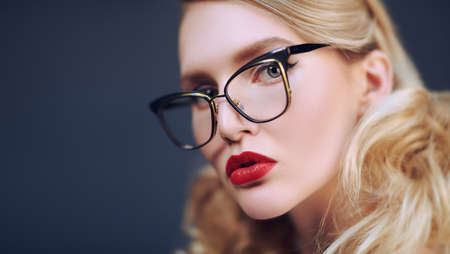 Close-up portrait of a blond fashionable blonde woman in elegant glasses. Optics. Business style.