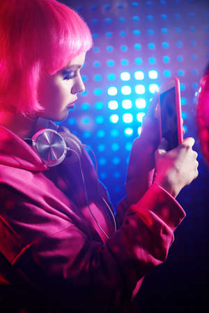 Bright girl with bright glitter make-up and pink hair communicates on social networks relaxing in a nightclub. Mixed color light. Disco style.