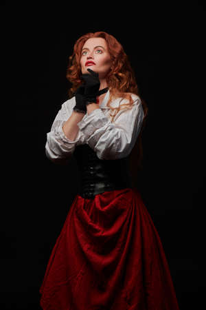 Portrait of a magnificent redhead woman in a historical costume of 16-17th centuries looking up on a black background. Reconstruction of the Middle ages.