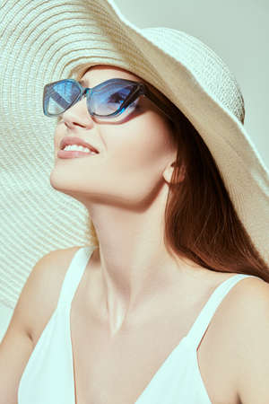 Close up of charming girl in a white dress and elegant hat with wide brim poses on a white background. Sunglasses. Summer fashion.