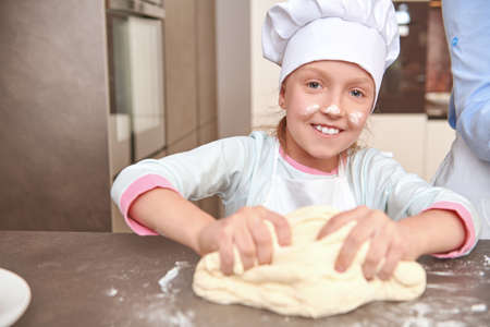 Happy little girl make dough for baking in the kitchen at home. Happy family. Healthy food at home.