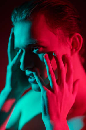 Close up portrait of a emotional young man shirtless in multicolored lights. Man's beauty and health. Art portrait.