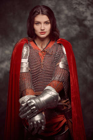 Portrait of a beautiful female knight in armor of noble birth. History of the Middle Ages. Art portrait on a grunge background.