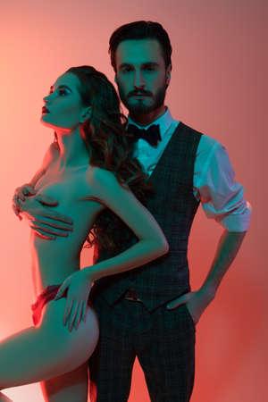 Handsome impassive man in elegant suit hugs girl. Love and fashion.