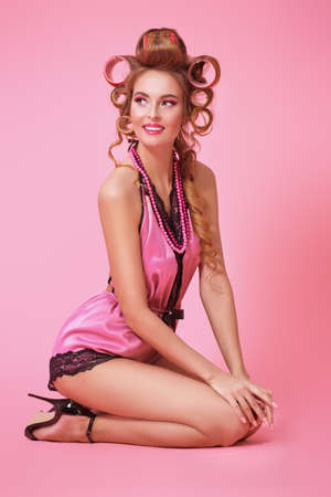 Full length portrait of a pretty woman in pink lingerie and with curlers in her hair over pink background. Beauty, fashion concept. Pin-up style.