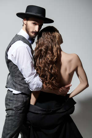 Sexual girl and handsome man posing back on grey background. Fashion and love.