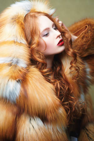 Portrait of a beautiful young woman with long red hair posing in a luxurious fox fur coat. Fur coat fashion. Archivio Fotografico