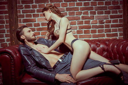 Love and relationships. A couple of passionate young people making love on a leather sofa in loft apartment. Glamorous lifestyle. Zdjęcie Seryjne