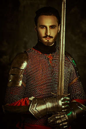 Medieval knight holds sword and armor on a black background. Standard-Bild