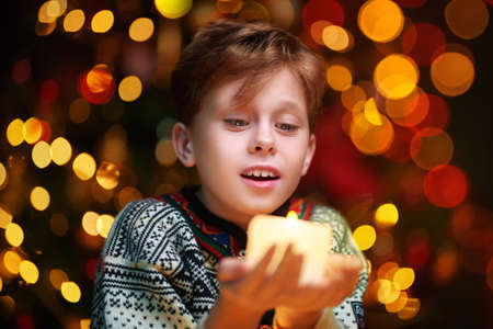 Close up portrait of a cheerful boy holding a burning candle candle. Lights and sparkle is around. Merry Christmas and Happy New Year!