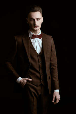 Elegant handsome man in classic suit and bow tie on a black background. Business style. Men's fashion. Archivio Fotografico