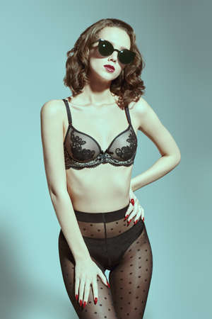 Attractive young woman poses in black lingerie and sunglasses. Studio shot. Underwear fashion. Imagens