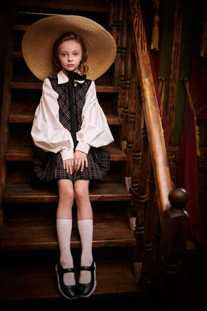Lovely girl in elegant classic school uniform and wide-brimmed straw hat sits on the steps in a classic vintage interior. British style. Kid's fashion.