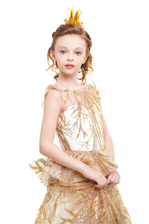 Portrait of a beautiful little princess girl in a golden dress and a crown on a white background. Childhood dreams. Fairy tales.