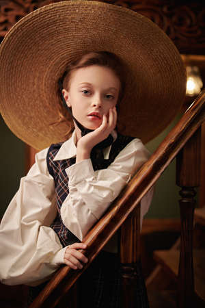 Portrait of a beautiful girl in elegant classic school uniform and wide-brimmed straw hat sits on the steps in a classic vintage interior. British style. Kid's fashion. 免版税图像