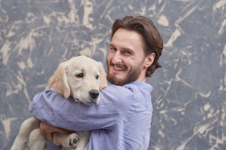 Portrait of a happy young man hugging his Golden Retriever dog on grunge background. A man and a pet.