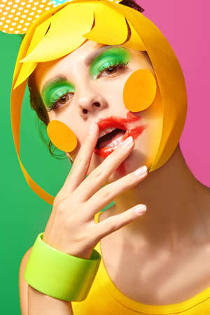 Bright make-up and cosmetics. Close up portrait of a fashionable beauty girl with colorful paper makeup and hairstyle and smudged lipstick on green and fuchsia background.