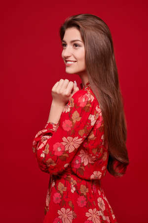 Charming happy girl in bright summer dress on a red background. Love and Valentine's Day. Banco de Imagens