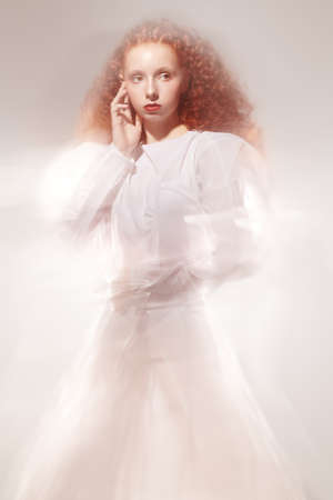 Art portrait of a refined female model with lush red curly hair posing in a long white futuristic dress among haze on light background.