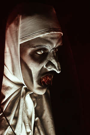 Close-up portrait of a devilish scary nun with terrible teeth. Halloween and Horrors. Standard-Bild