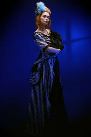 Full length portrait of a beautiful red-haired woman in a 19th century dress on a dark blue background. Fashion history, makeup and hairstyle.