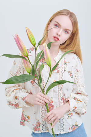 Beautiful blonde girl in a summer blouse poses with lily flowers with closed buds on a white background. Light fresh makeup in pink colors. Perfume and cosmetics.