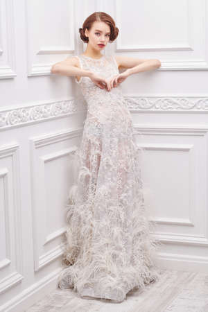 Stunning young woman in a white wedding dress posing in a white room with classic interior. Full length portrait. Wedding fashion.