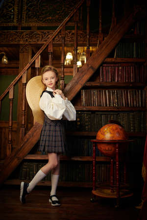 Full length portrait of a girl child in elegant classic school uniform standing in a luxurious vintage library interior. Kid's school fashion. 免版税图像