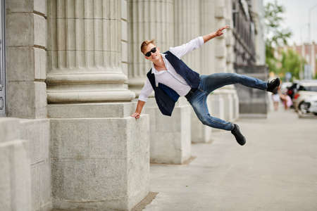 Handsome guy bounces with joy on the street. Summer fashion. Summer holidays and vacation.