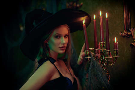 Portrait of a beautiful young witch in an old castle. Fairy tales. Halloween.