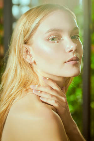 Close-up portrait of a beautiful tender girl with blonde hair and fresh shining makeup. Beauty and jewelry. Spa, skincare and cosmetics.