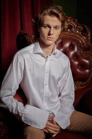 Luxury lifestyle. Portrait of a handsome young man in elegant white shirt sitting in an armchair in a luxury apartments. Men's beauty, fashion.