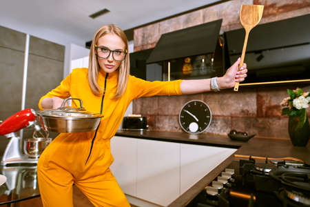 Pretty young woman preparing dinner at home in the kitchen. Modern interior, furniture for the kitchen. Cook at home. Healthy eating and diet.
