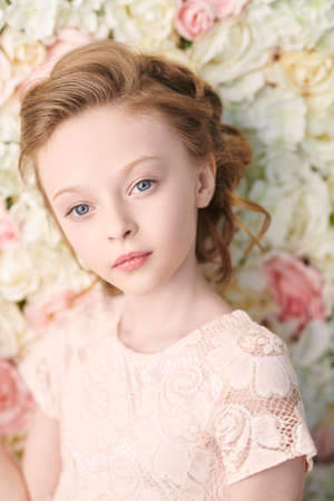 Lovely little girl in a soft pink dress stands by a floral background of white and pink roses. The mood of spring and summer. Kid's fashion. Foto de archivo