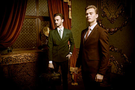 Two handsome young men in elegant classic suits stand in a luxury apartments with classic interior. Men's beauty, fashion. Фото со стока
