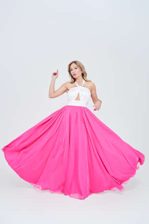 Gorgeous middle-aged woman in a lush evening dress on a white background. Evening fashion. Full length studio portrait. 免版税图像