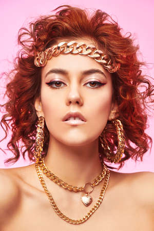 Portrait of an attractive tanned girl with fine curls and large gold jewelry on a pink background. Beauty and jewelry. Hairstyle.