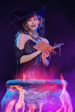 Halloween magic. A beautiful young witch in a hat and elegant dress conjures over a cauldron surrounded by magical fires. Foto de archivo