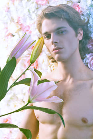 Handsome young man with blond wavy hair posing with tender pink and white lilies and roses in haze. Perfumery and beauty products. Men's beauty. 免版税图像