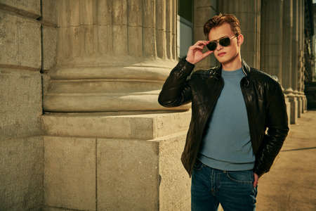 Handsome confident young man in sunglasses and leather jacket walks along the city street against the background of an old building. Men's fashion. Lifestyle. 免版税图像
