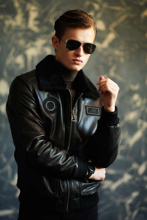 Men's style. Portrait of a handsome man in black leather jacket and sunglasses on a grunge background. 免版税图像