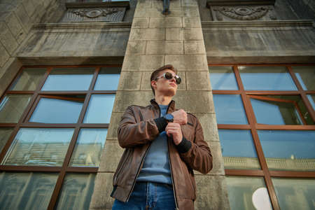 Men's fashion. Stylish young man in sunglasses and leather jacket stands on a city street and looks at his wristwatch. Lifestyle. 免版税图像