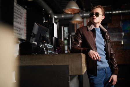 Handsome young man in a leather jacket and sunglasses spends time in a bar. Lifestyle. Men's fashion.