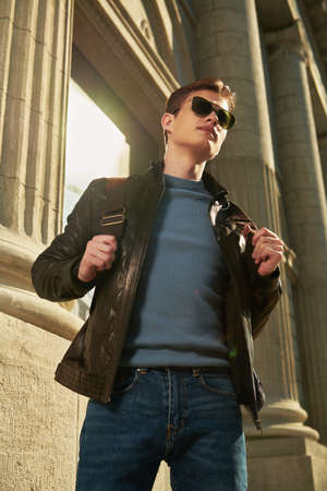 Men's fashion. Confident and stylish young man in sunglasses and leather jacket stands on a city street. Lifestyle. 免版税图像