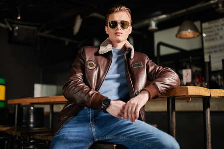 Stylish young man in a leather jacket and jeans spends time in a bar. Men's fashion. Lifestyle.