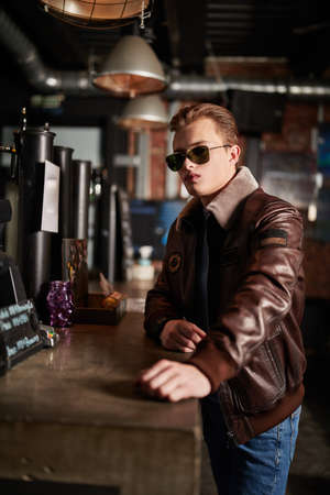 Lifestyle. Stylish young man in a leather jacket and jeans spends time in a bar. Men's fashion.