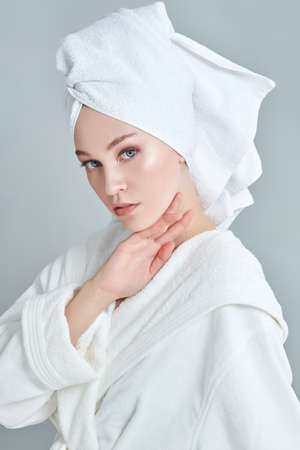 Beauty, body care, spa. Portrait of a beautiful young woman in a white bathrobe and a towel around her hair after a shower.