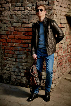 Men's fashion. Full length porttrait of a handsome stylish man in sunglasses and leather jacket standing on a city street by a brick wall.