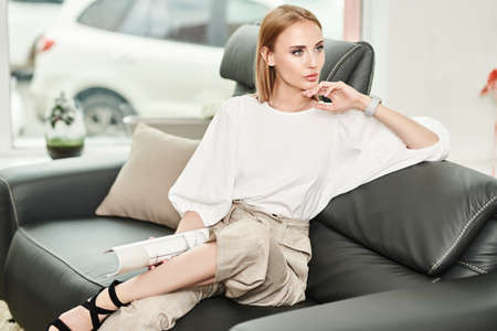 Furniture and interior. Beautiful young woman sits on a leather sofa in a modern interior. Elegant business style. 免版税图像