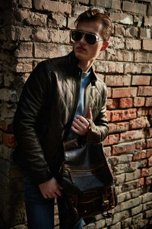 Confident and stylish young man in sunglasses and leather jacket stands on a city street by a brick wall. Men's fashion. Lifestyle.
